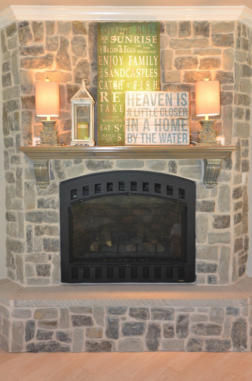 Corner stone fireplace. Lake house design. Reclaimed wood accents.