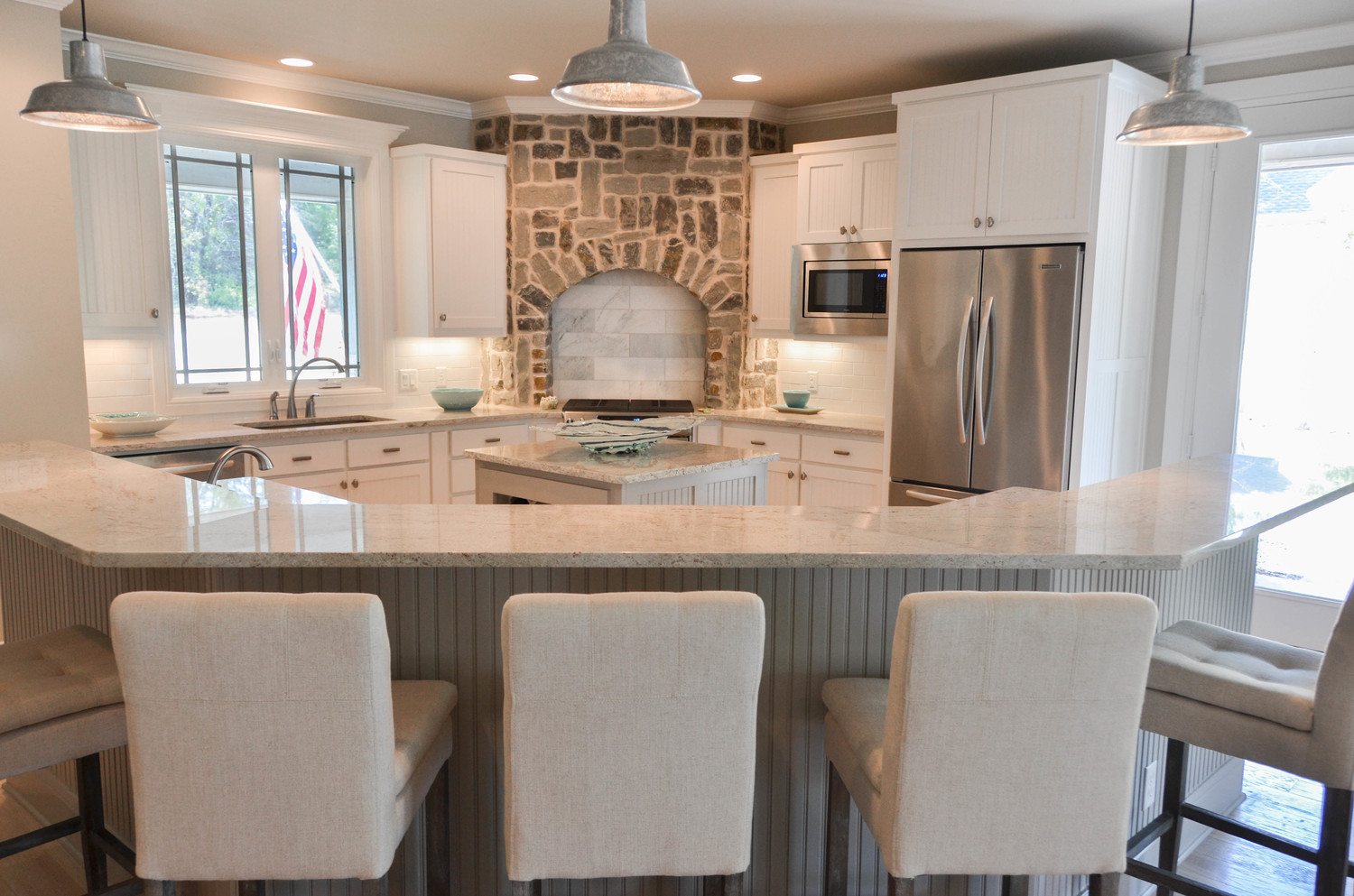Custom farmhouse kitchen design with a stone vent hood and linen barstools