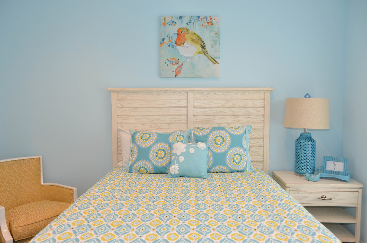 Yellow and blue bedroom with a whimsical bird art.