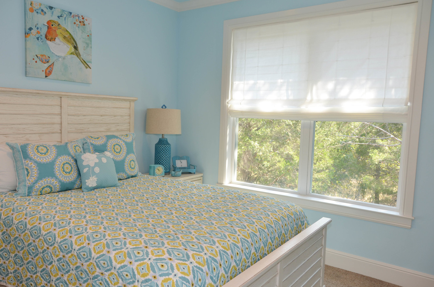 Roman shades in a light blue and yellow bedroom. White shiplap headboard.