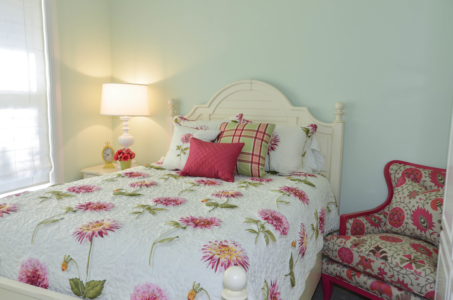 Traditional bedroom with white wood poster bed. Hot pink floral fabric.