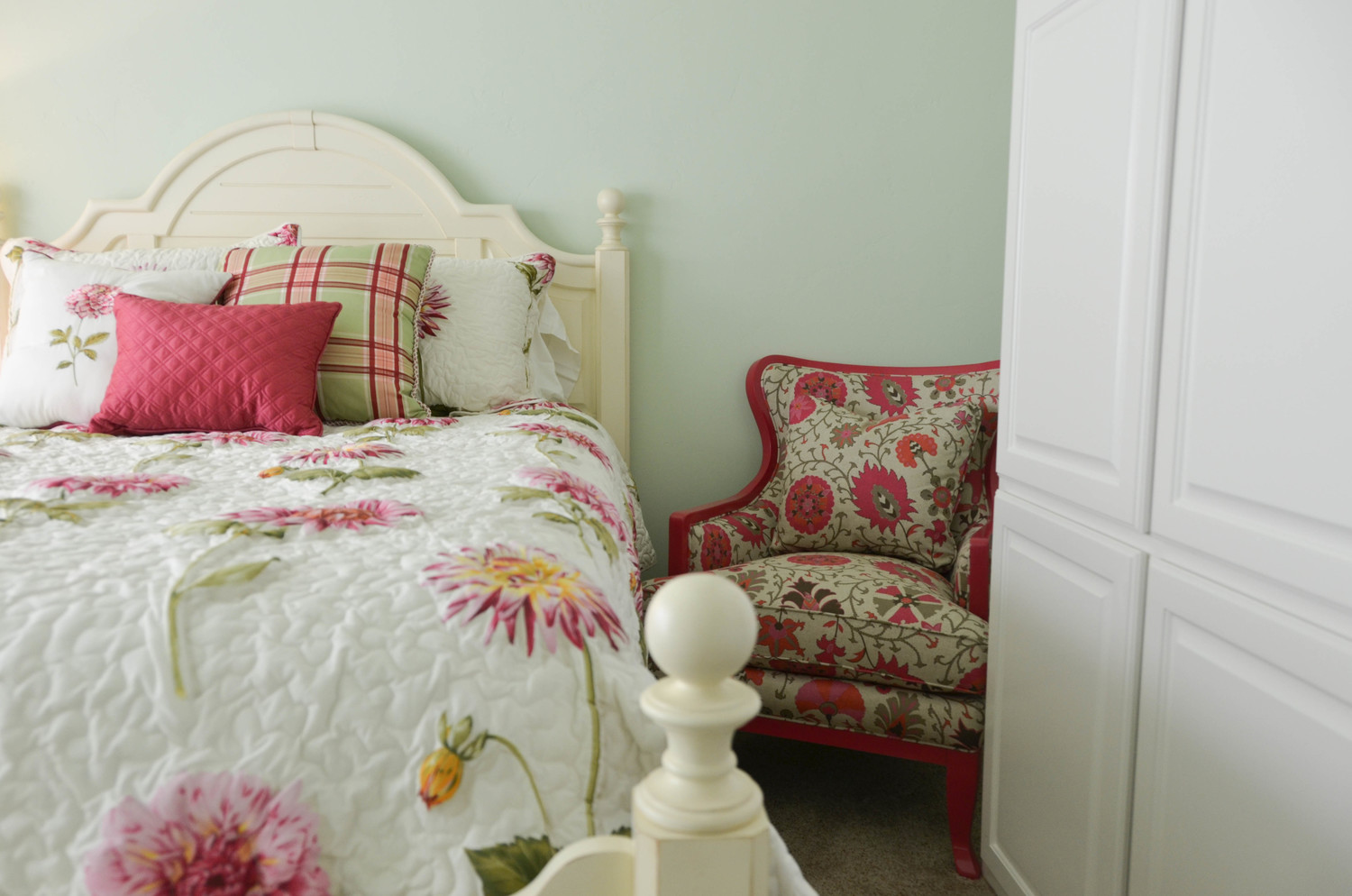 Traditional mint and pink interior design. White wood poster bed.