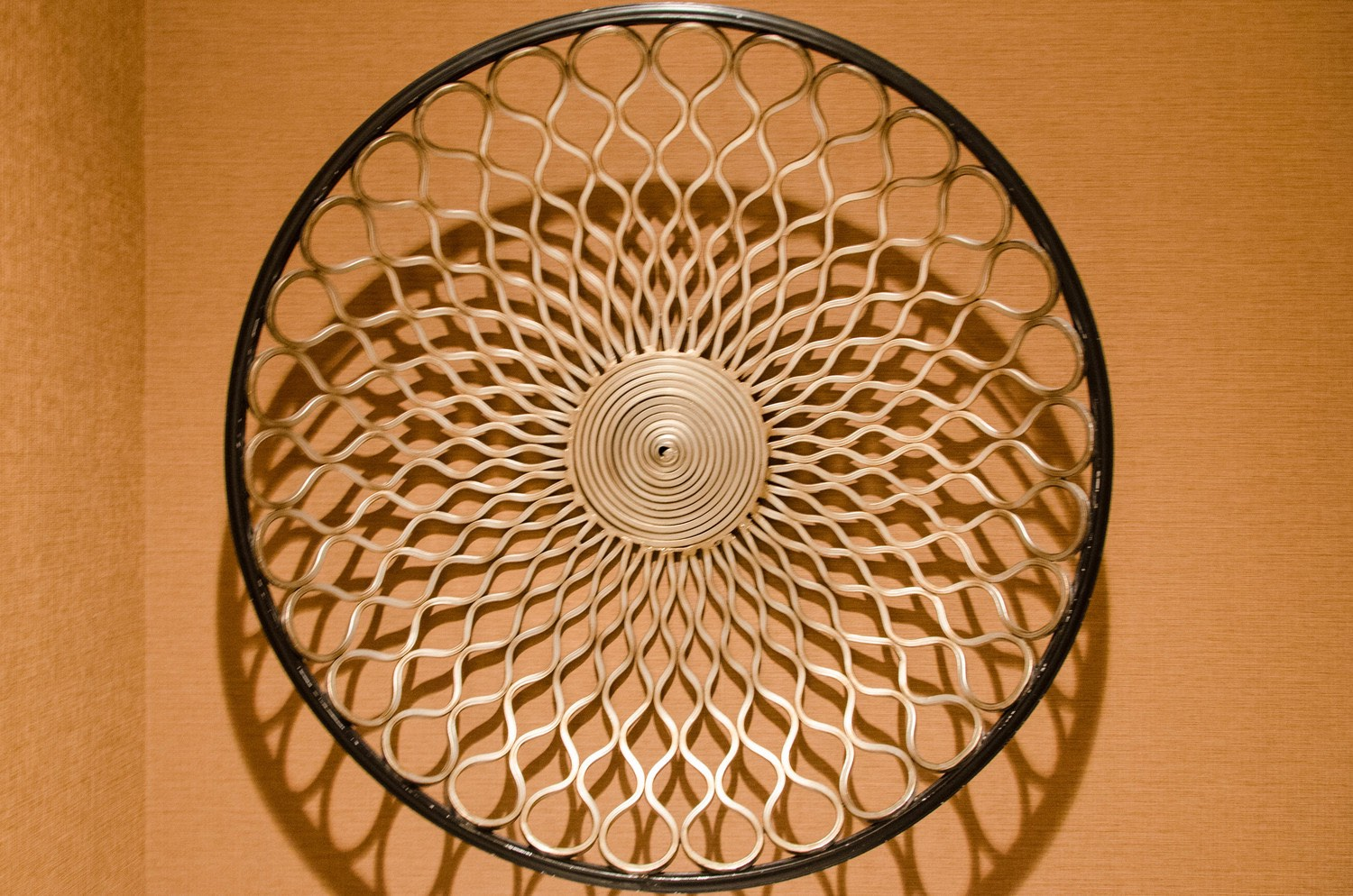 Metal woven bowl used as wall art