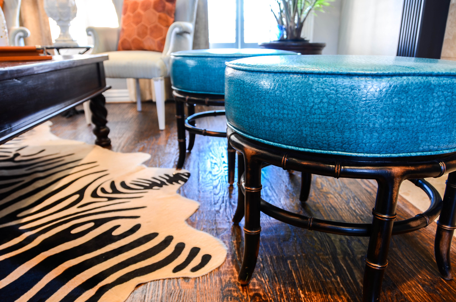 Teal leather ottomans and zebra hide rug