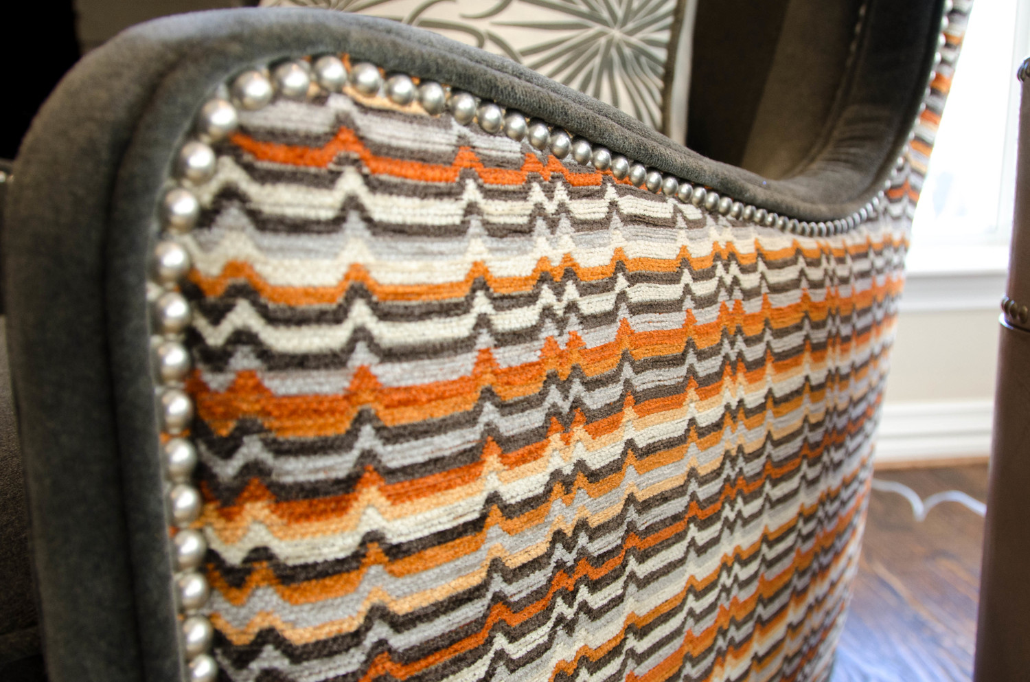 Contrasting orange fabric on a wing chair with nail heads