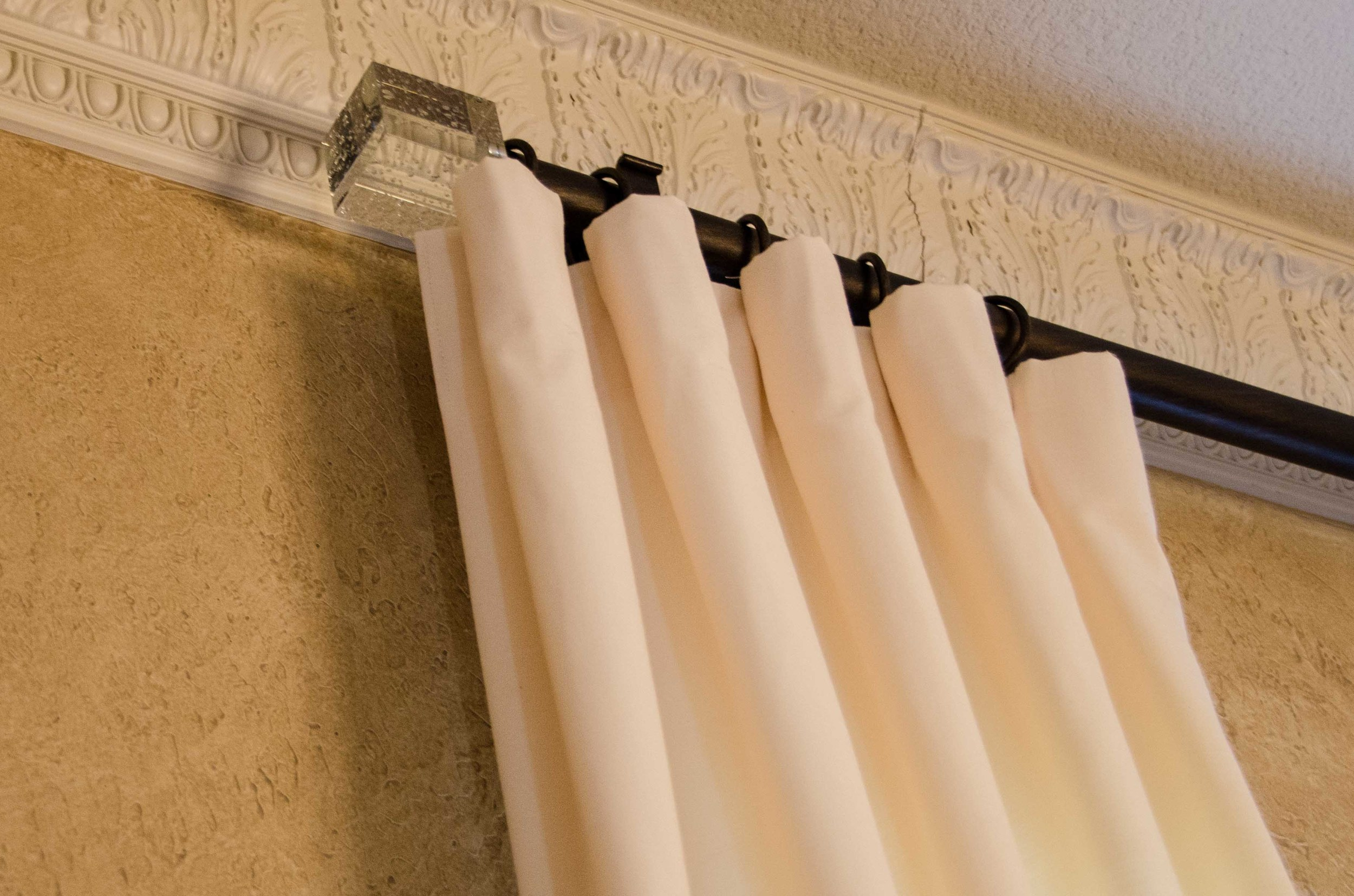 Custom designed draperies with oil rubbed bronze hardware and crystal finials