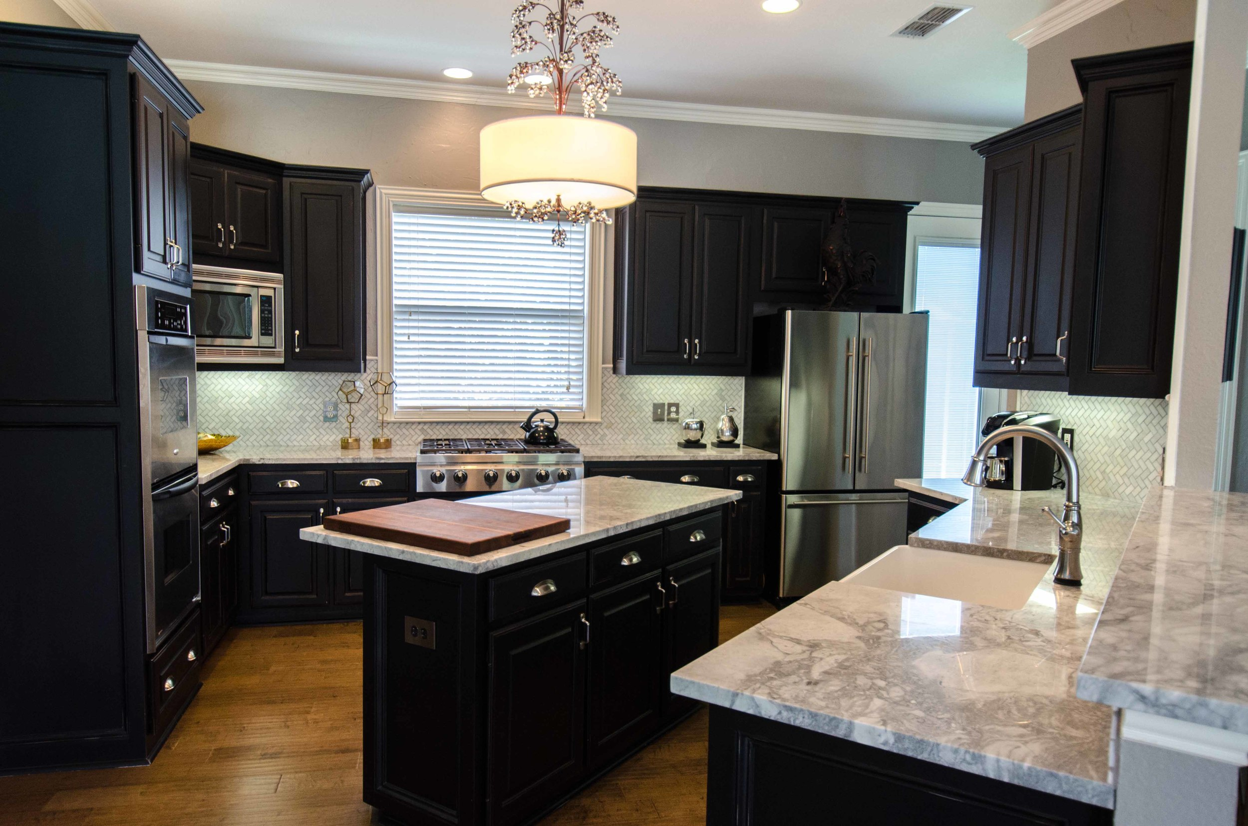 Kitchen with black cabinets and marble counters