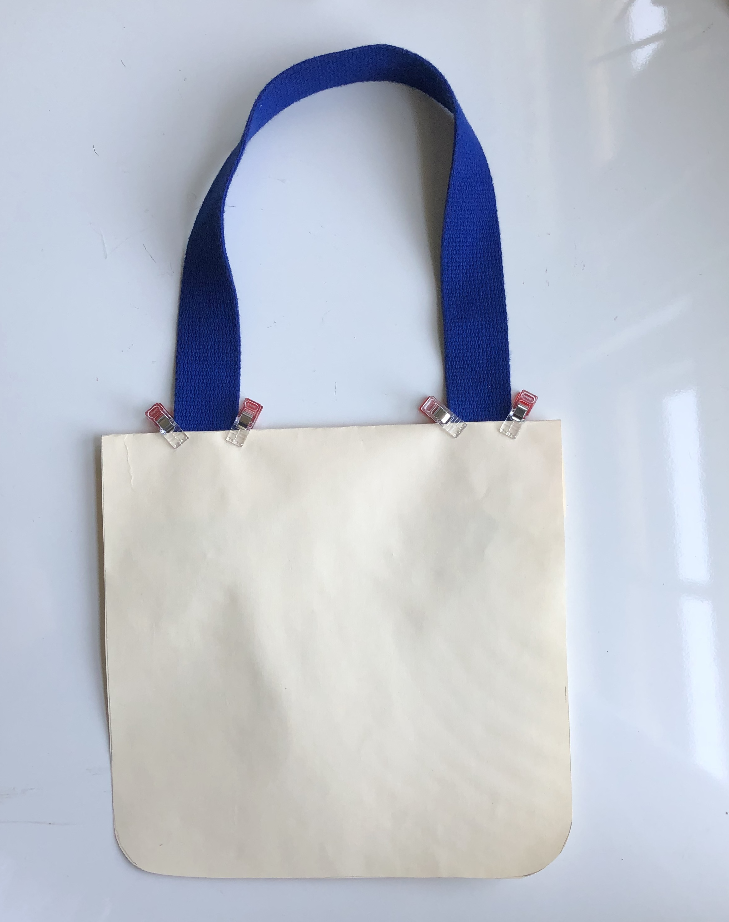 A tote mock-up made of oaktag. Handles are clipped to the top to test for fit.