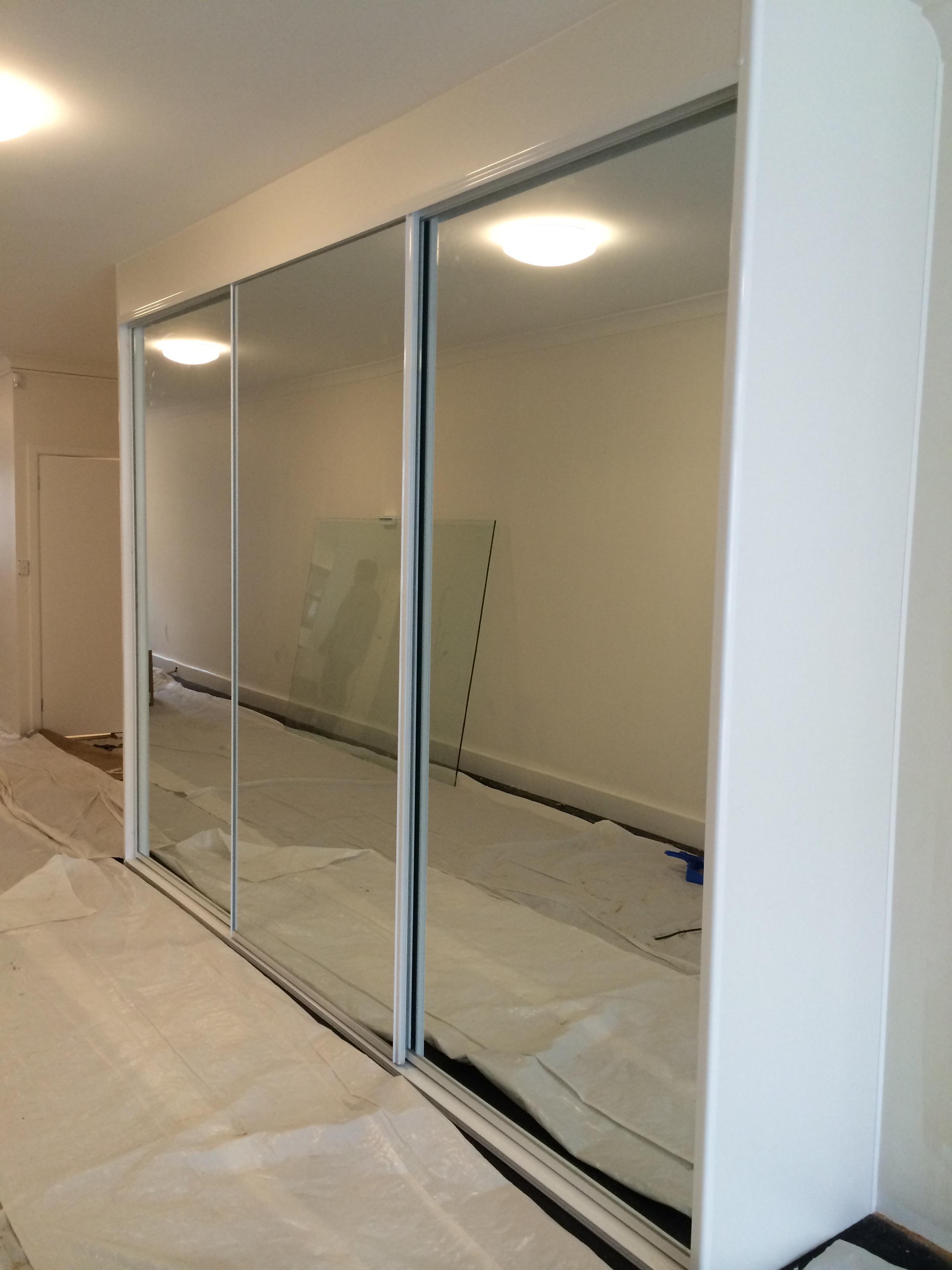 three door sliding mirror wardrobe with white frame.JPG