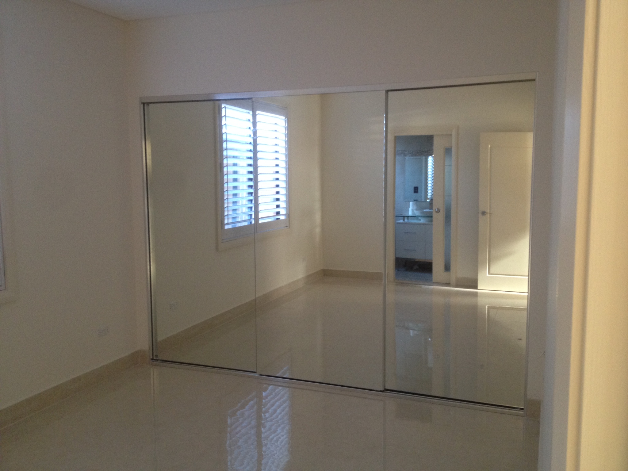 wall to wall wardrobe with mirror doors and white frame.JPG