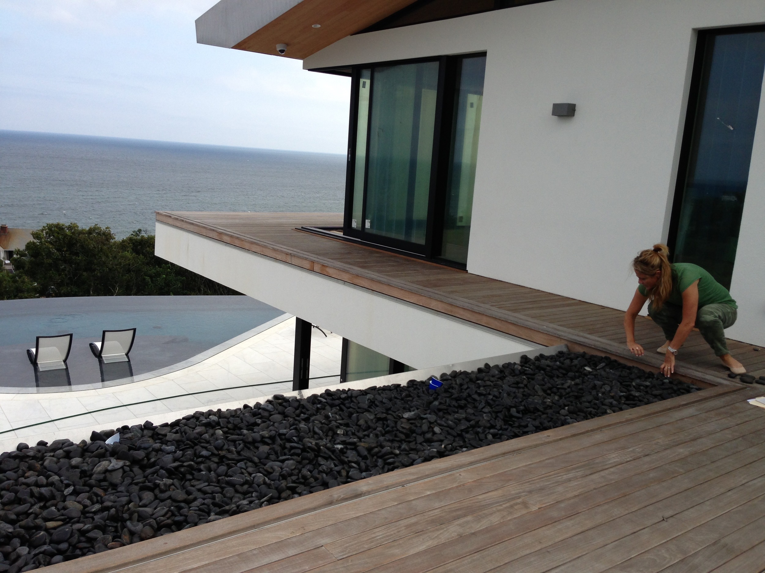 Steph selecting a river rock from the Roof Deck to be used as a model for the Living Room coffee table.