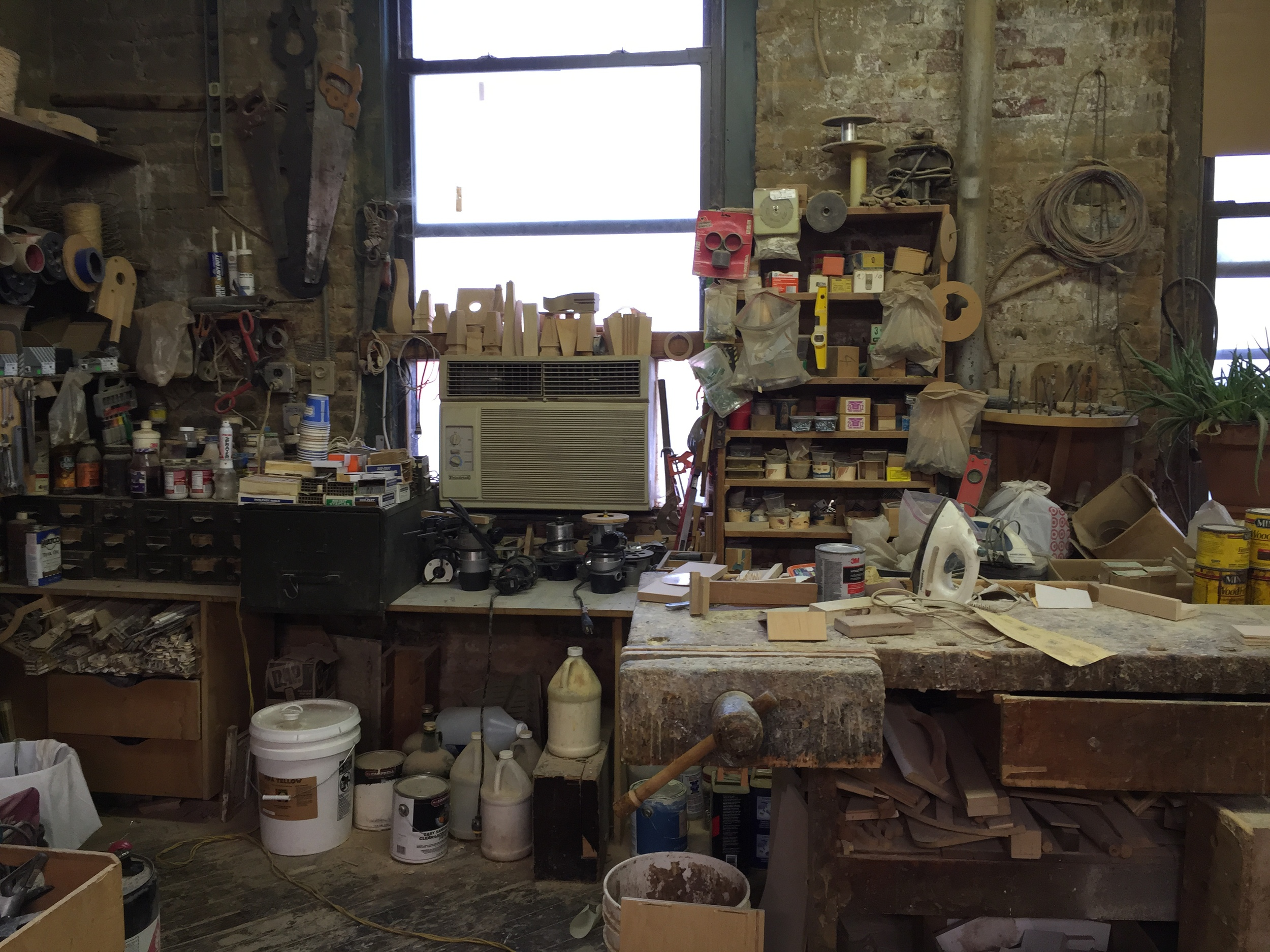 This area of his shop shows a well worn workbench, and evidence of year upon year of collecting tools, hardware and the paraphernalia required to make each piece of his handmade furniture.