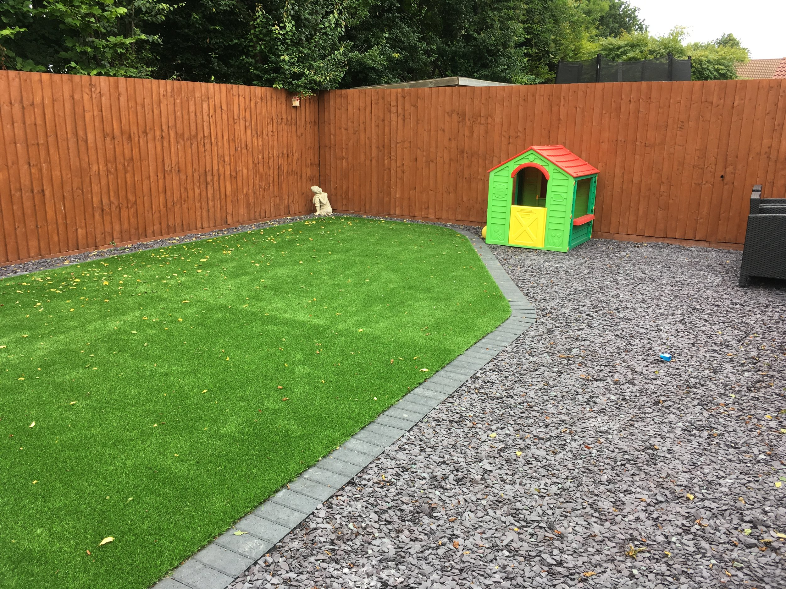 Artificial turf with block border, slate patio & fencing (Upton)