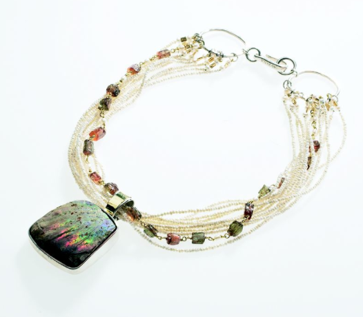Fossilized ammonite pendant strung with multiple seed pearls and Andalusite beads