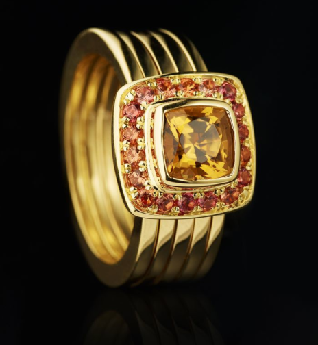 Renaissance ring of a cushion yellow sapphire surrounded by orange sapphires