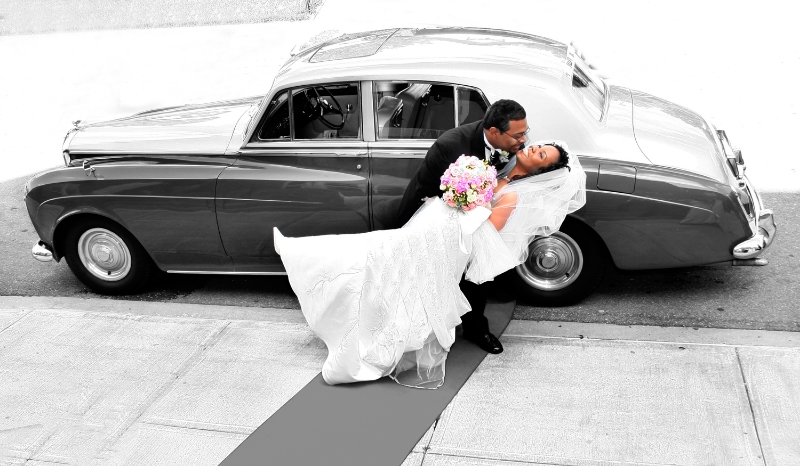Couple kissing in front of classic car