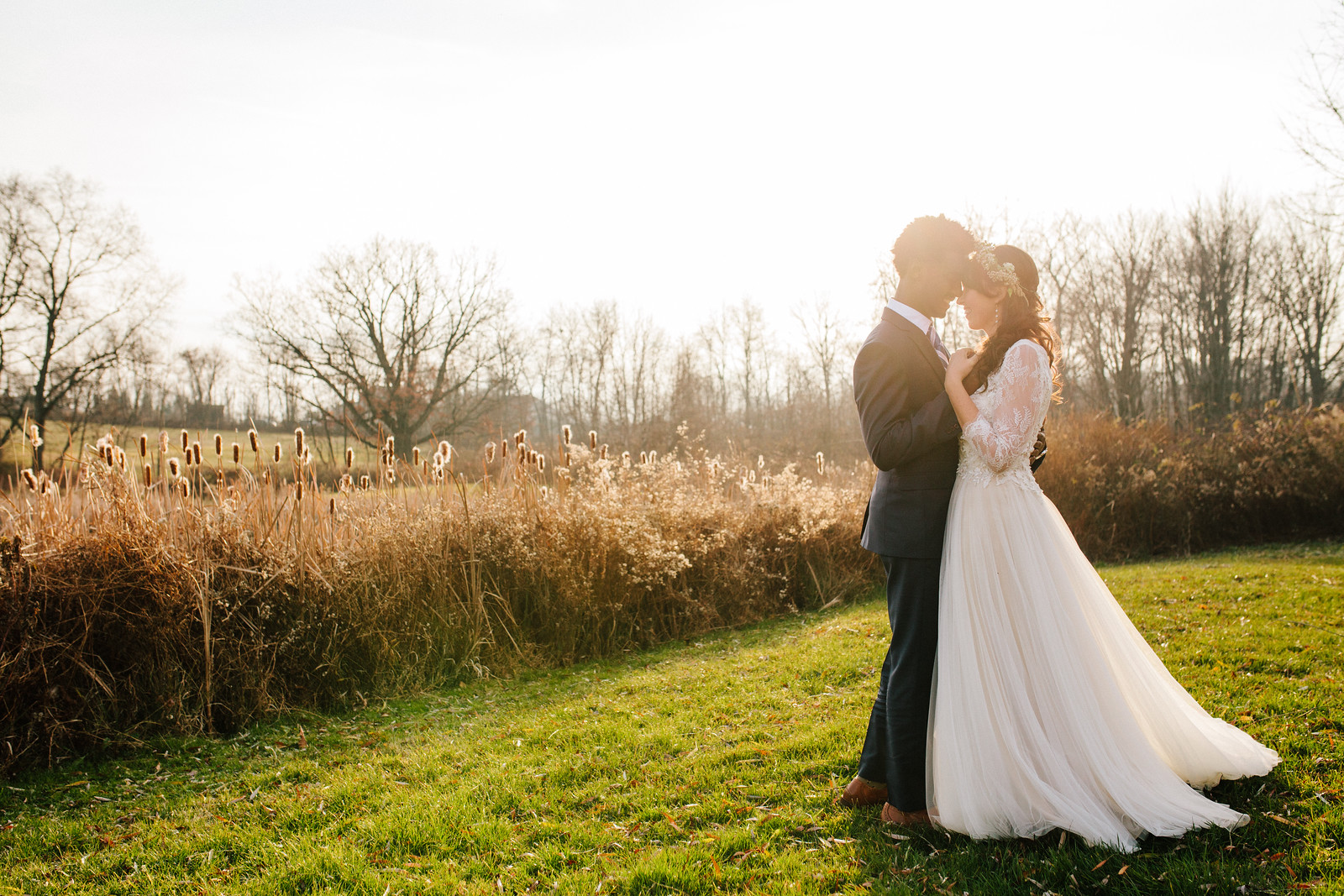A Bride and groom standing in a meadow looking lovingly into each others eyes