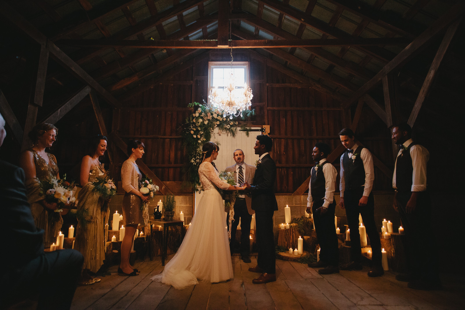 Winter barn wedding with candles, a floral arch, chandelier and the wedding party laughing