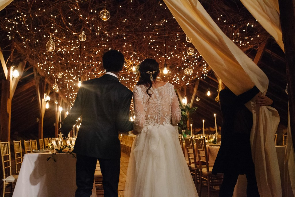 A bride and groom looking at the over the top lighted ceiling of their barn wedding