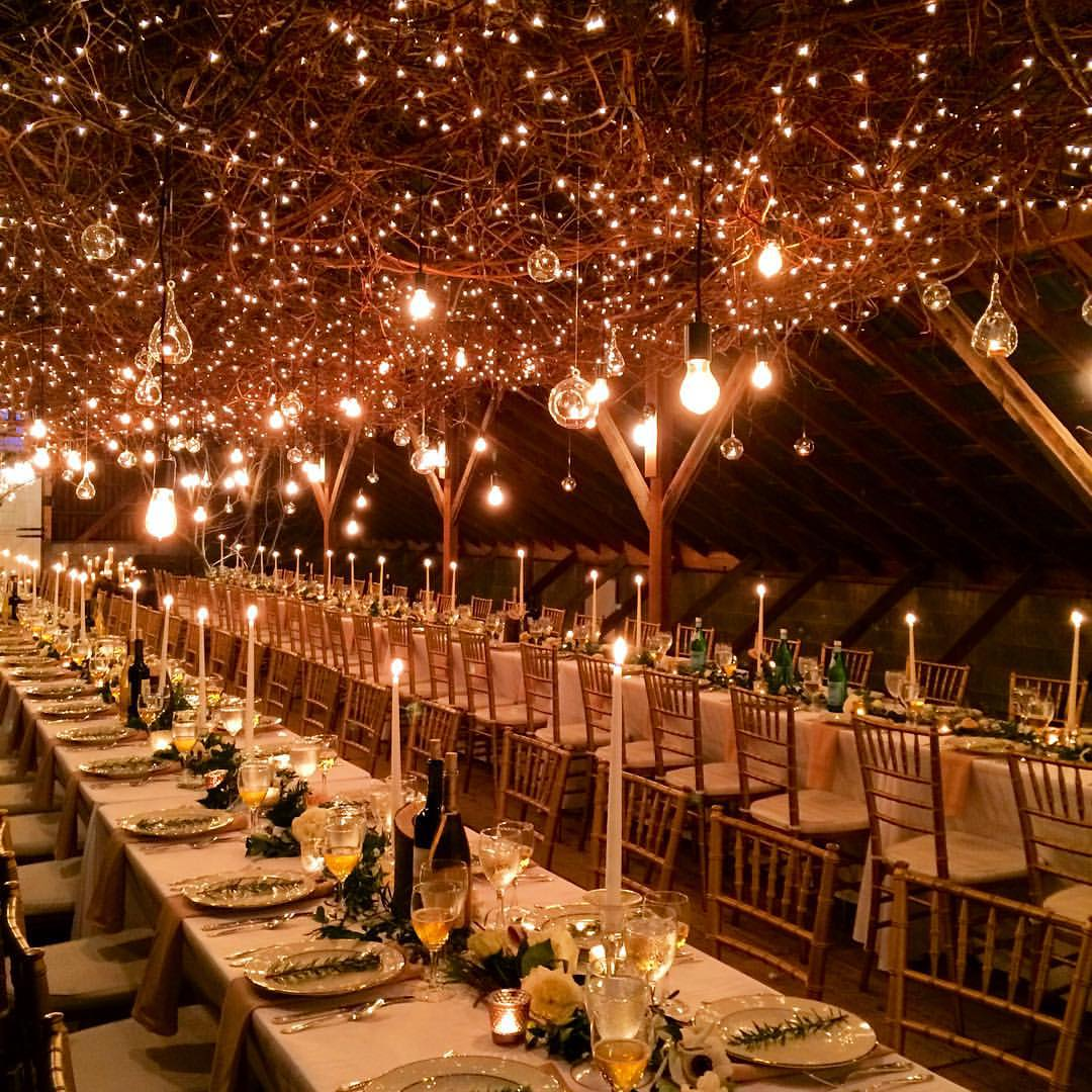 A beautiful lighted barn ceiling with twinkle lights, Edison bulbs, hanging candles and beautiful tables