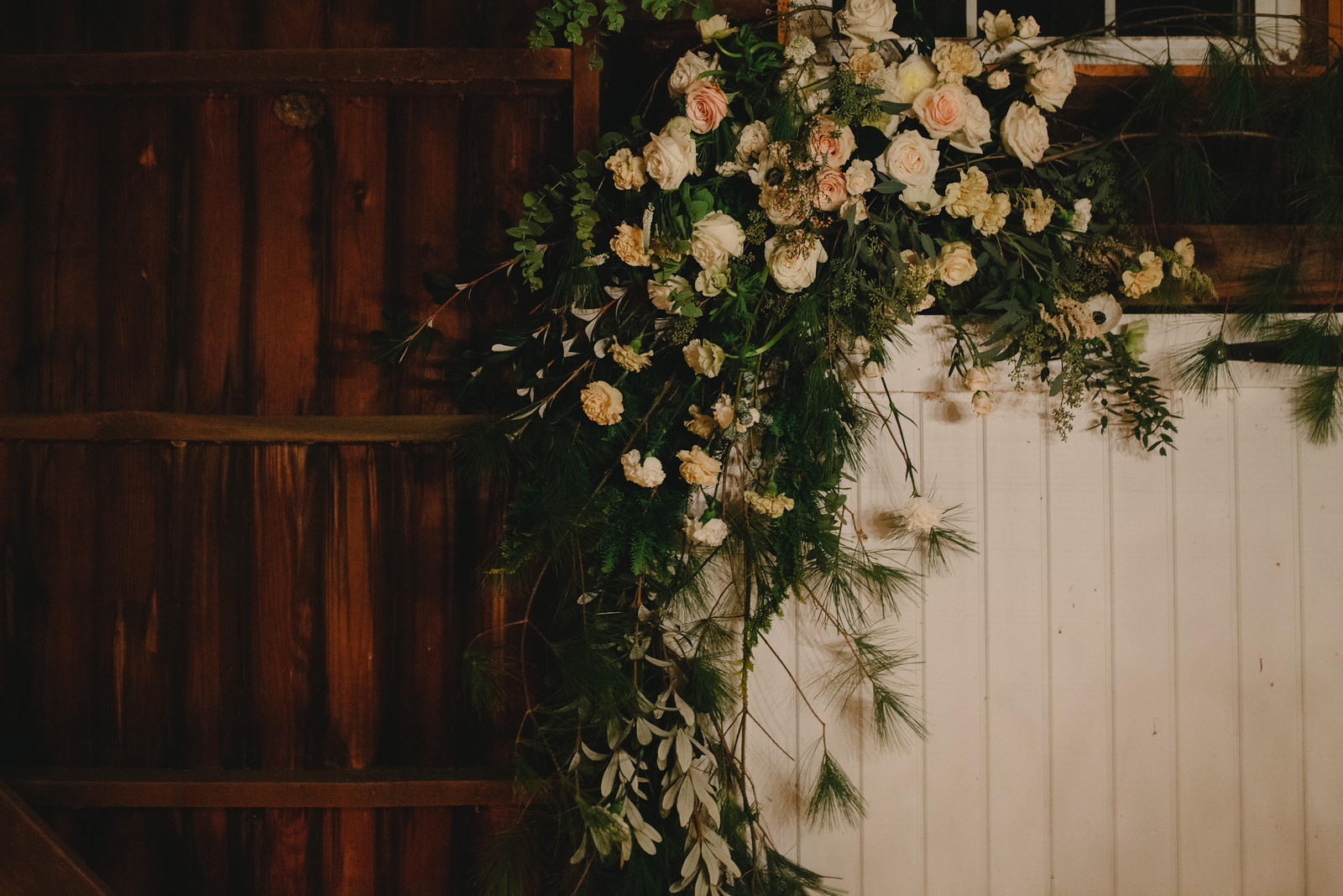 A natural wedding floral arch over a barn door for a winter wedding