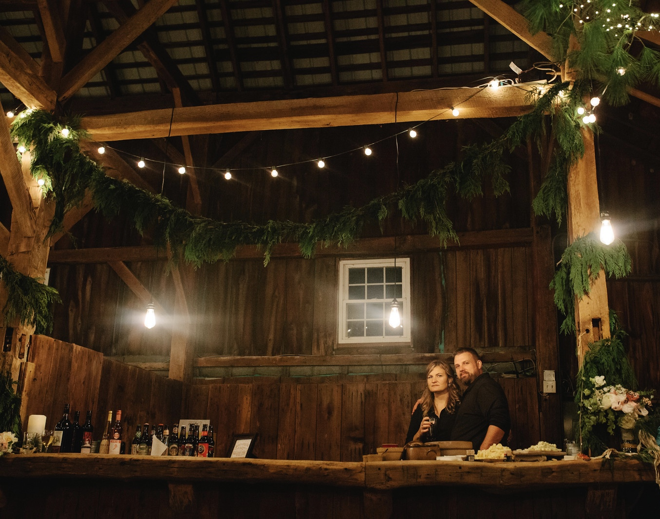 A super cool couple bartending at a winter barn reception with hanging greens