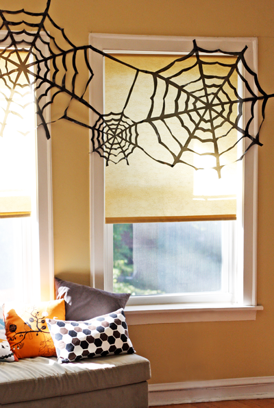 Image via  How About Orange   For the procrastinator in all of us, these quick and simple  spiderwebs  bring a classic Halloween touch to any room - tons of time or dollars  NOT  required. Just literally grab a black trash bag, a pair of scissors and some tape. Get cutting and hang. Similar to snowflakes during winter, grab the kids and put them to work! These spiderwebs make quite the splash in the foyer or above a picture window.