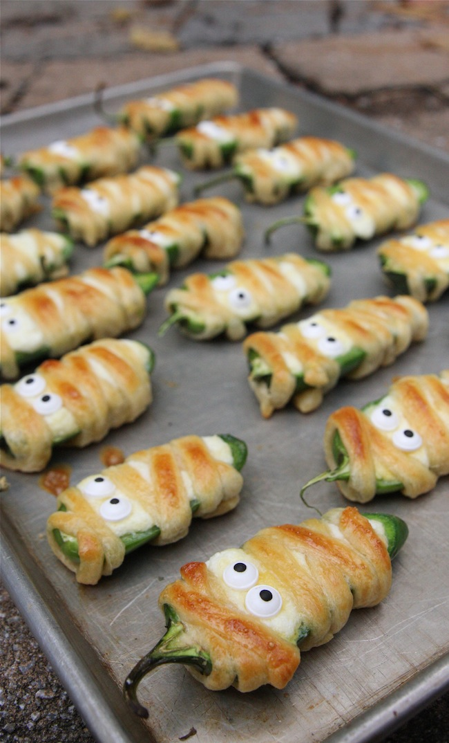 Image via  The Hopeless Housewife   Not only are these  jalapeño party snacks  the perfect quick bite but they are just the right amount of cute and creepy to have your guests coming back for more! Allow only 8 to 10 minutes in the oven, these poppers are best served warm and straight off the pan. A little touch of savory goes a long way on one of the sweetest holidays around.