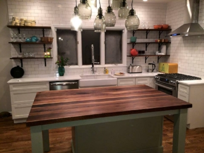 Black walnut island and shelves, subway tile, floating hood, apron sink and spring faucet. hand crafted by craftsman reclaimed