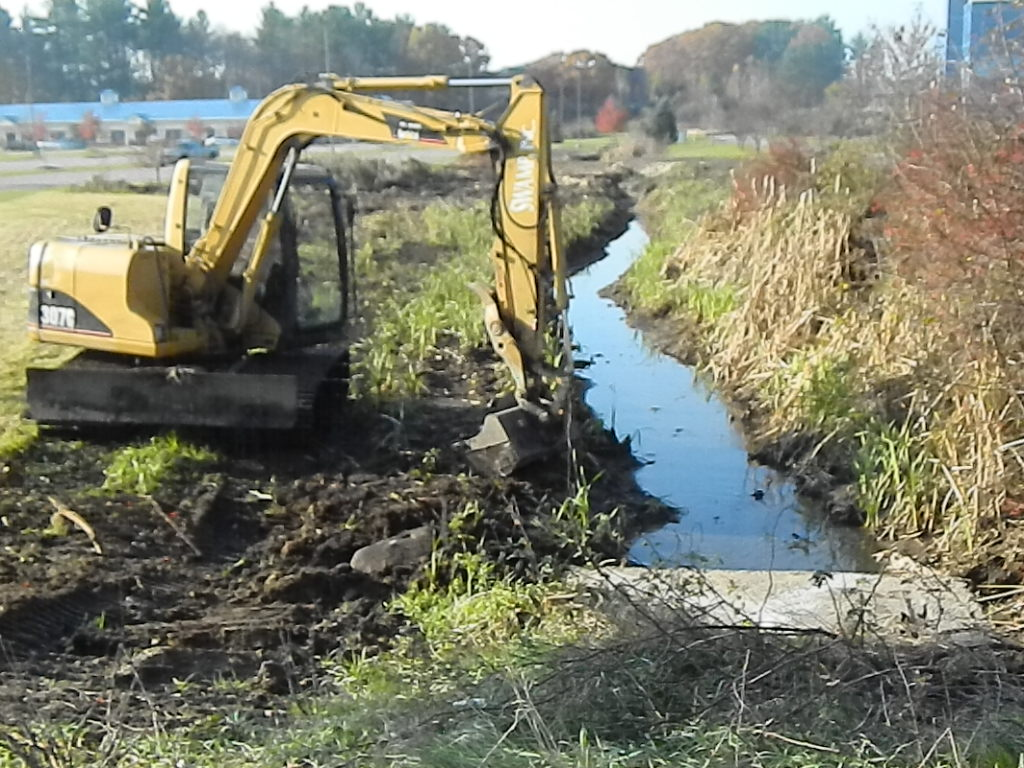 Restoring a poorly flowing drainage ditch with our excavator.