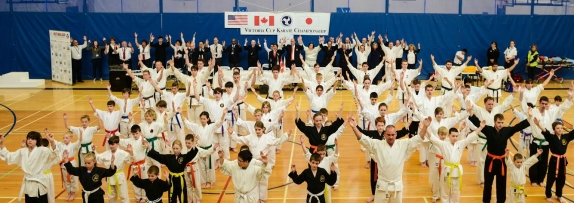 "Competitors and officials raise their arms in the shape of a ""Y"" in support of     Yoshukai founder Soke Katsuo Yamamoto     Don Osborne Photography"