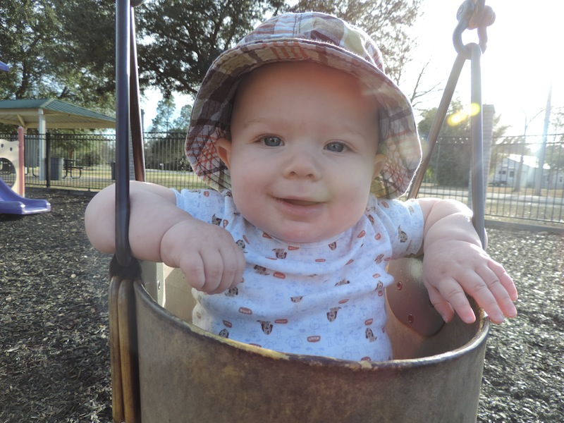 Issie in a bucket swing with the sun behind him while wearing a hat.JPG