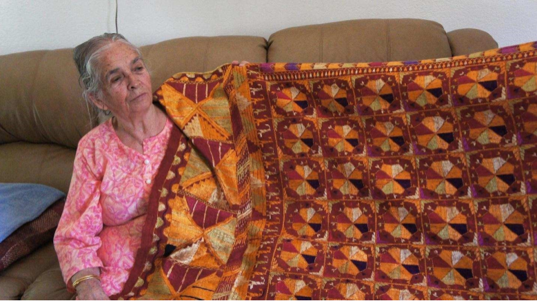 Amrik Kaur, age 83 with a phulkari that her mother hand-embroidered and passed down to her. Photo by Conner Singh Vanderbeek.