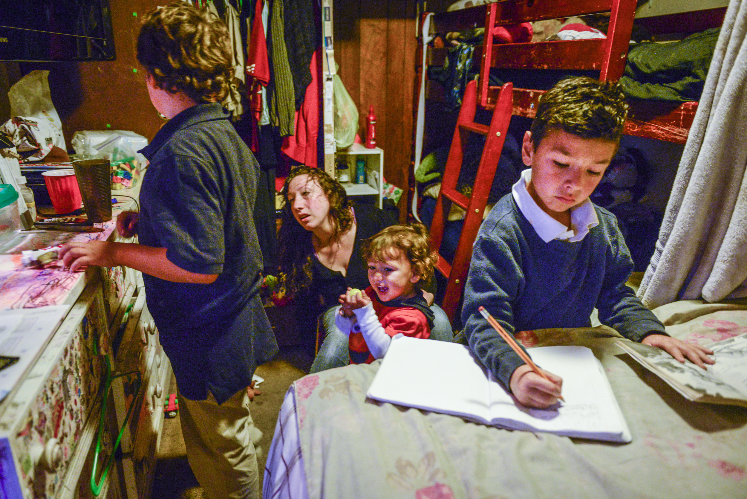Mateo, 7, finishes his homework while Amanda helps Dominic and Christopher get ready to go to school. The studio they live in is so small there is no room for a table. The kids do their homework on their bed.