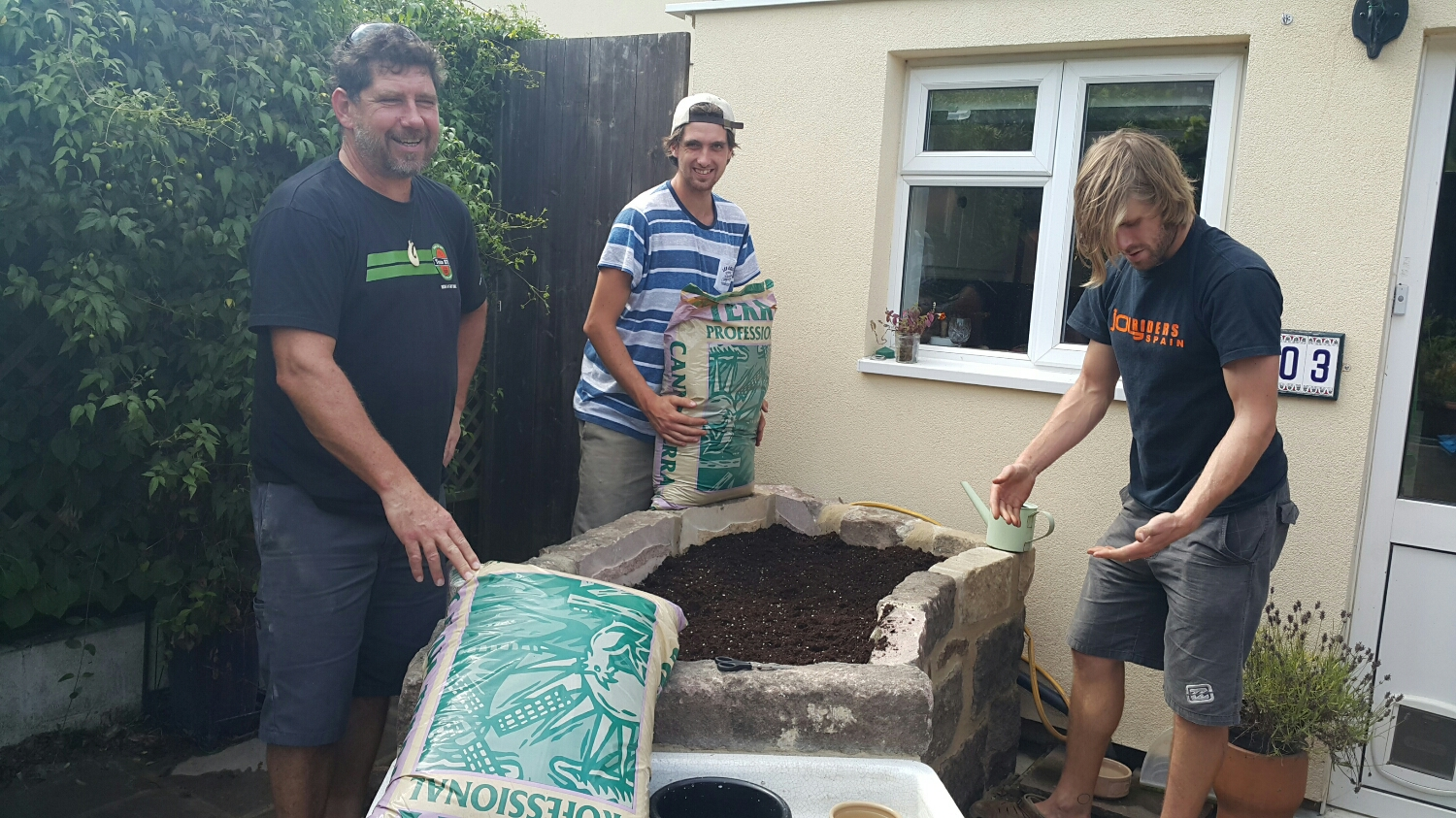 Ben doing all the Hard work filling in Wyns new Herb garden.  Pete not sure what the brown stuff is on his hands