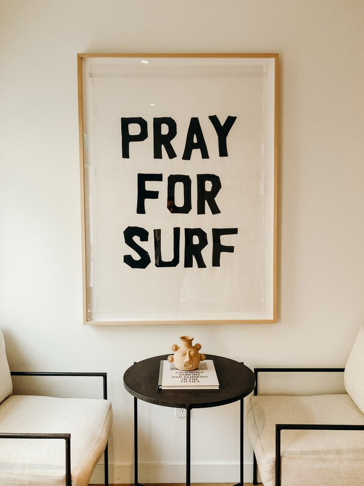 Pray for Surf Flag  hanging in Surfrider Hotel, next to Le Corbusier prints - as seen in Vogue Paris, Goop, Rip & Tan. Flags available from Tappan gallery in LA.