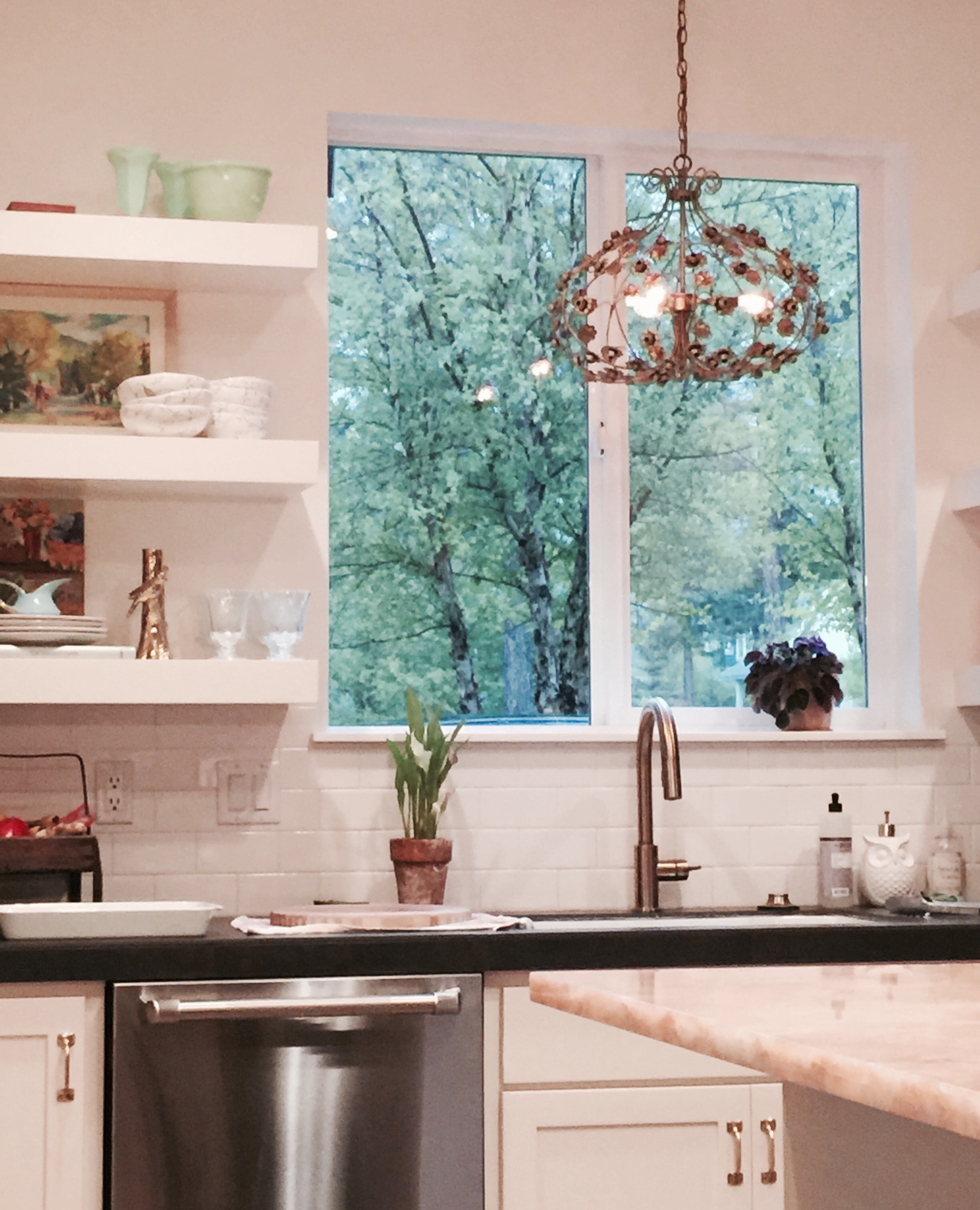My kitchen: featuring subway tile, onyx island, antique berry basket, vintage Italian pendant light, and  Carrie Geraci  art.
