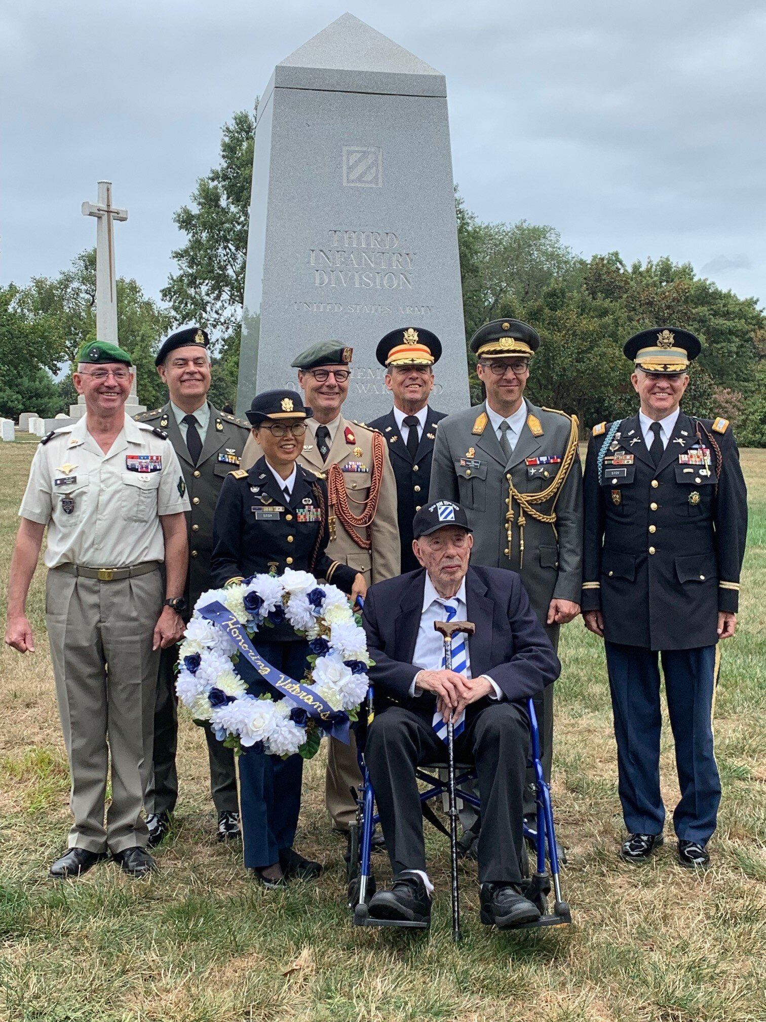 Before the 3rd Infantry Division Monument.  From left, standing: Major General Brice Haudet, former Defense Attaché of France, Colonel Vasileios Lampropoulos, Defense Attaché of Greece, Lieutenant Colonel Monika Stoy (President of the Out post International, Society of the 3rd Infantry Division) Colonel Paul Elverding, Defense Attaché of The Netherlands, Major General Jügen Ortner, Defense Attaché of Austria, Lieutenant Colonel Tim Stoy (President of the 15th Infantry Regiment Association).  Seated in front: U.S. Army veteran (WWII) Charlie Condron from New York, almost 95 years old, who fought all the way from Northern Africa, Sicily, Italy, Southern France, Germany, to Salzburg, Austria.