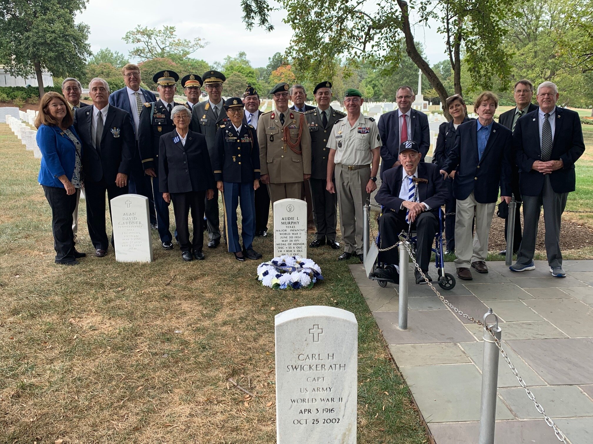 The attendees behind the headstone of Audie Murphy at Arlington National Cemetery.