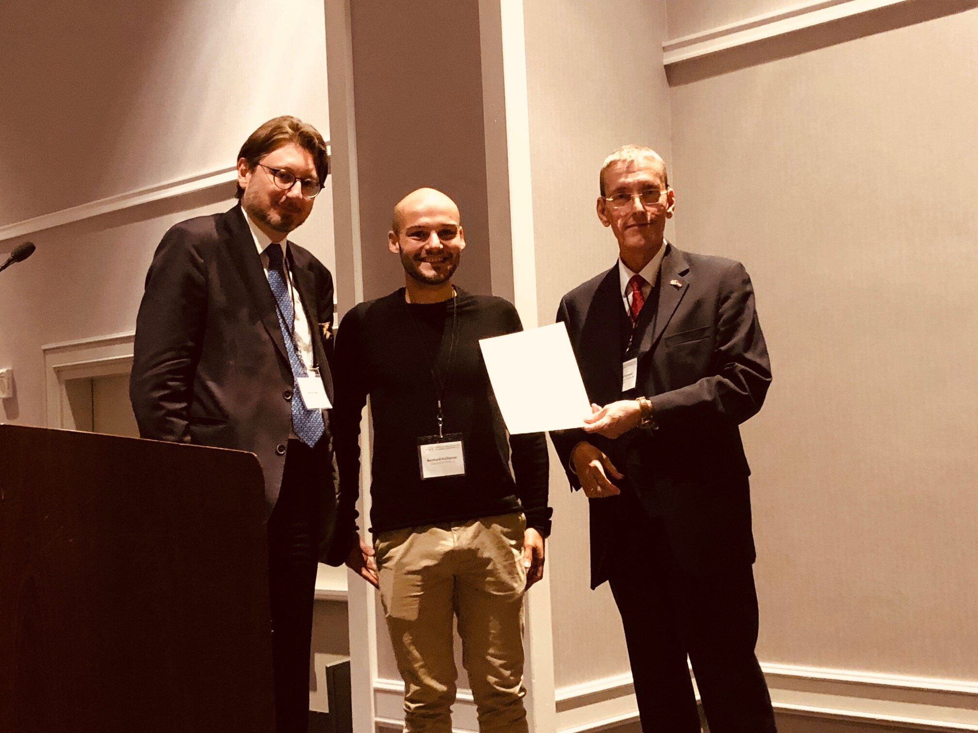 Dr. Michael Haider, Director of the Austrian Cultural Forum New York (left), and Dr. Christoph Ramoser, Head of the Science Ministry's International Department (right), present a grant to the University of Innsbruck's Bernhard Achhorner.