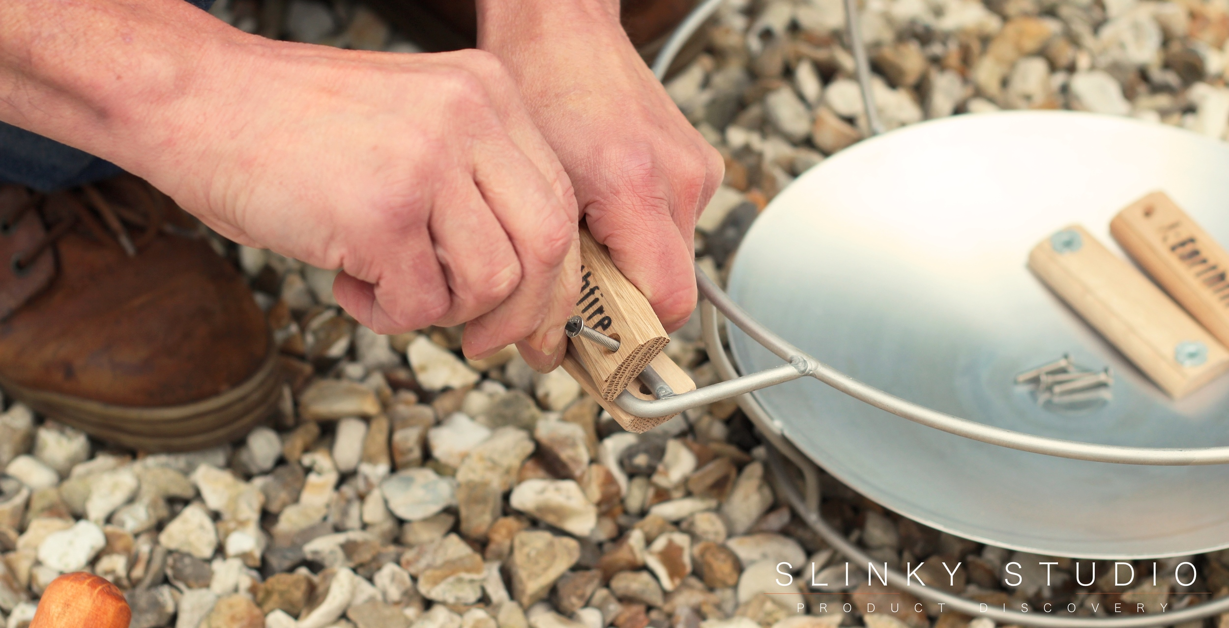 Grenadier Earth Fire Pizza Oven Screwing Handle On.jpg