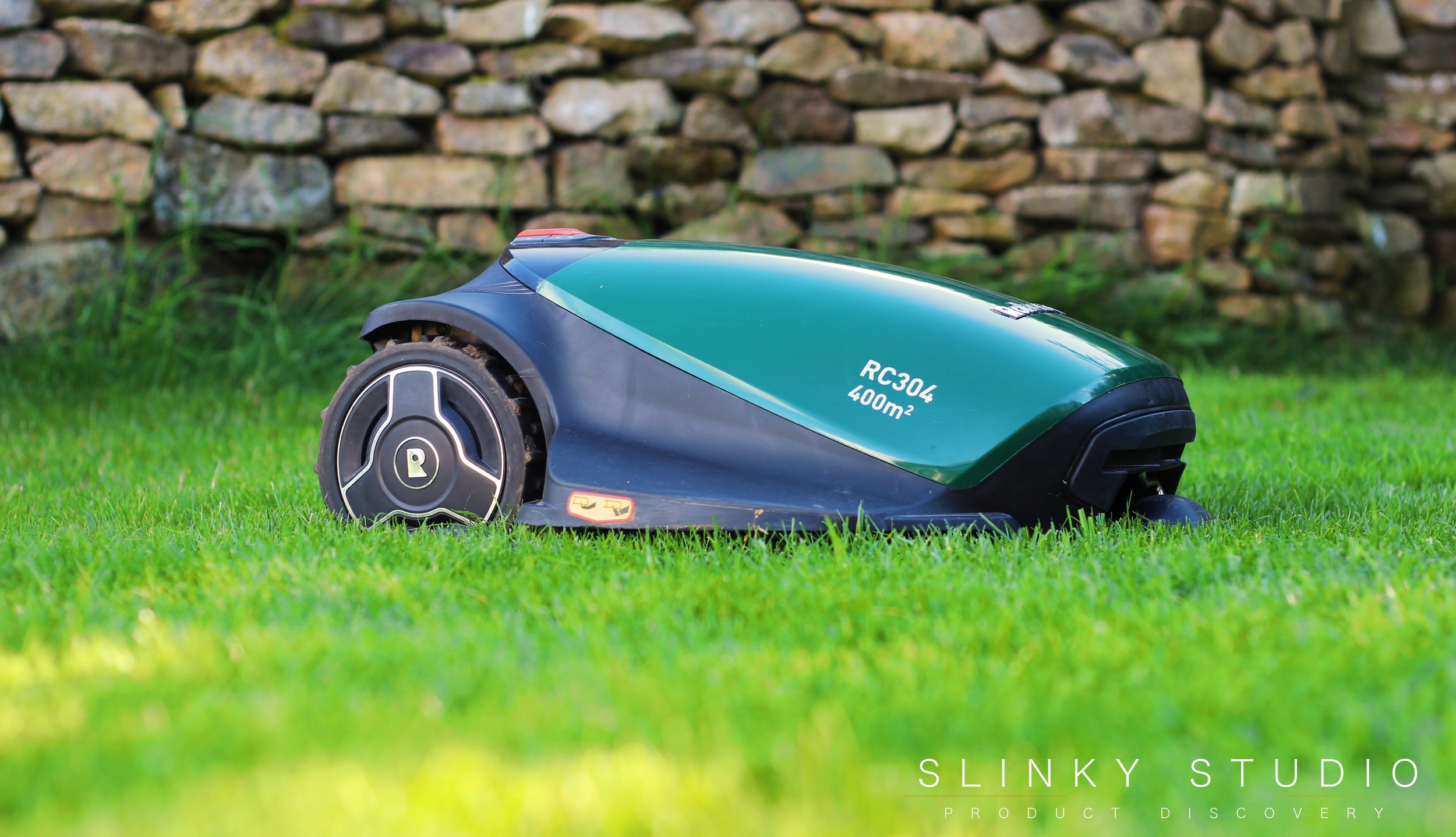 Robomow RC304 Robot Lawnmower Side View Cutting Lawn in Sun.jpg