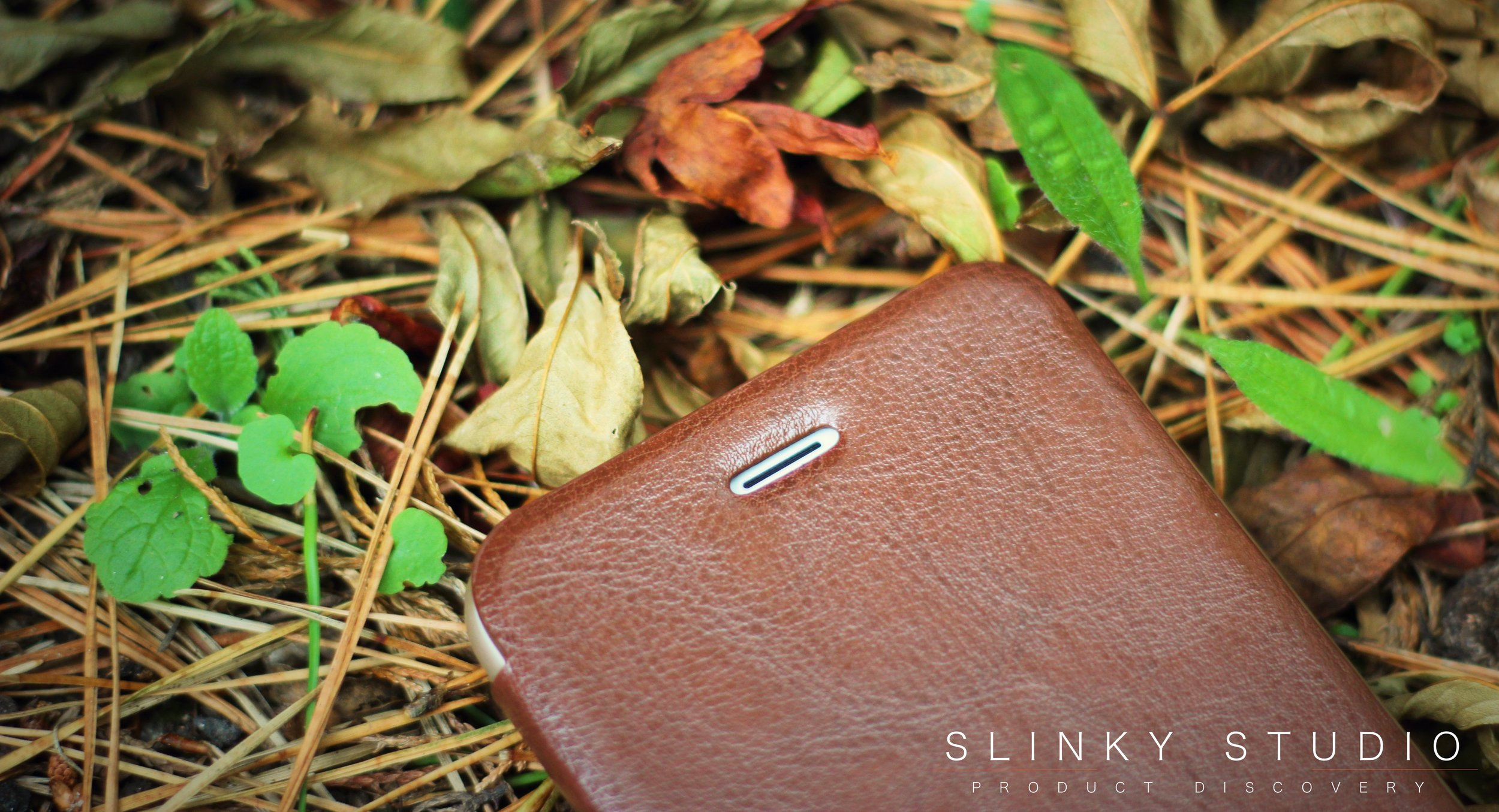 Elago Leather Flip Case for iPhone 6:6s Plus Front Speaker Cut Out Lying on Pile of Leafs.jpg