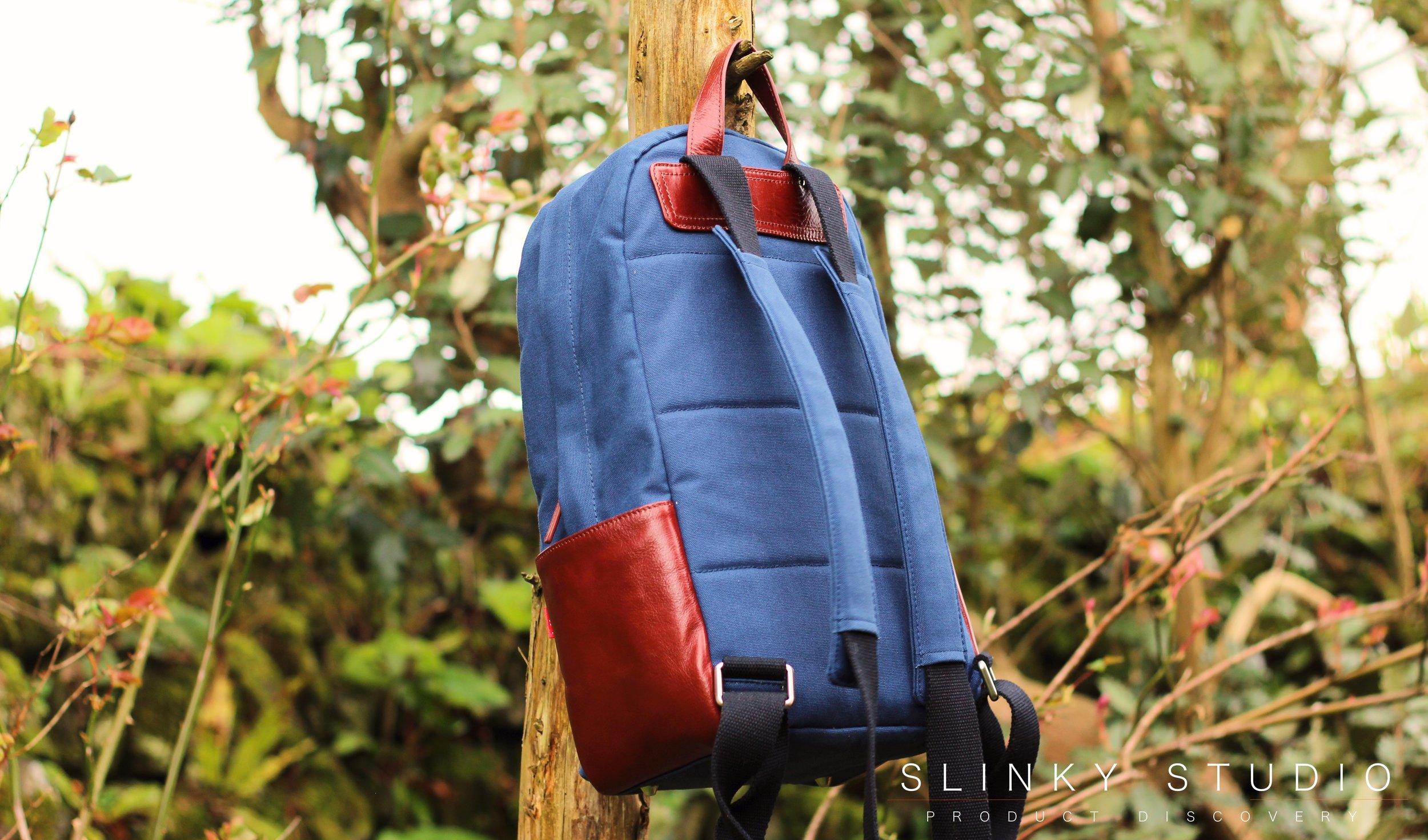Toffee Berlin Backpack hanging from Tree Branch Adjustable Shoulder Straps Navy Blue.jpg
