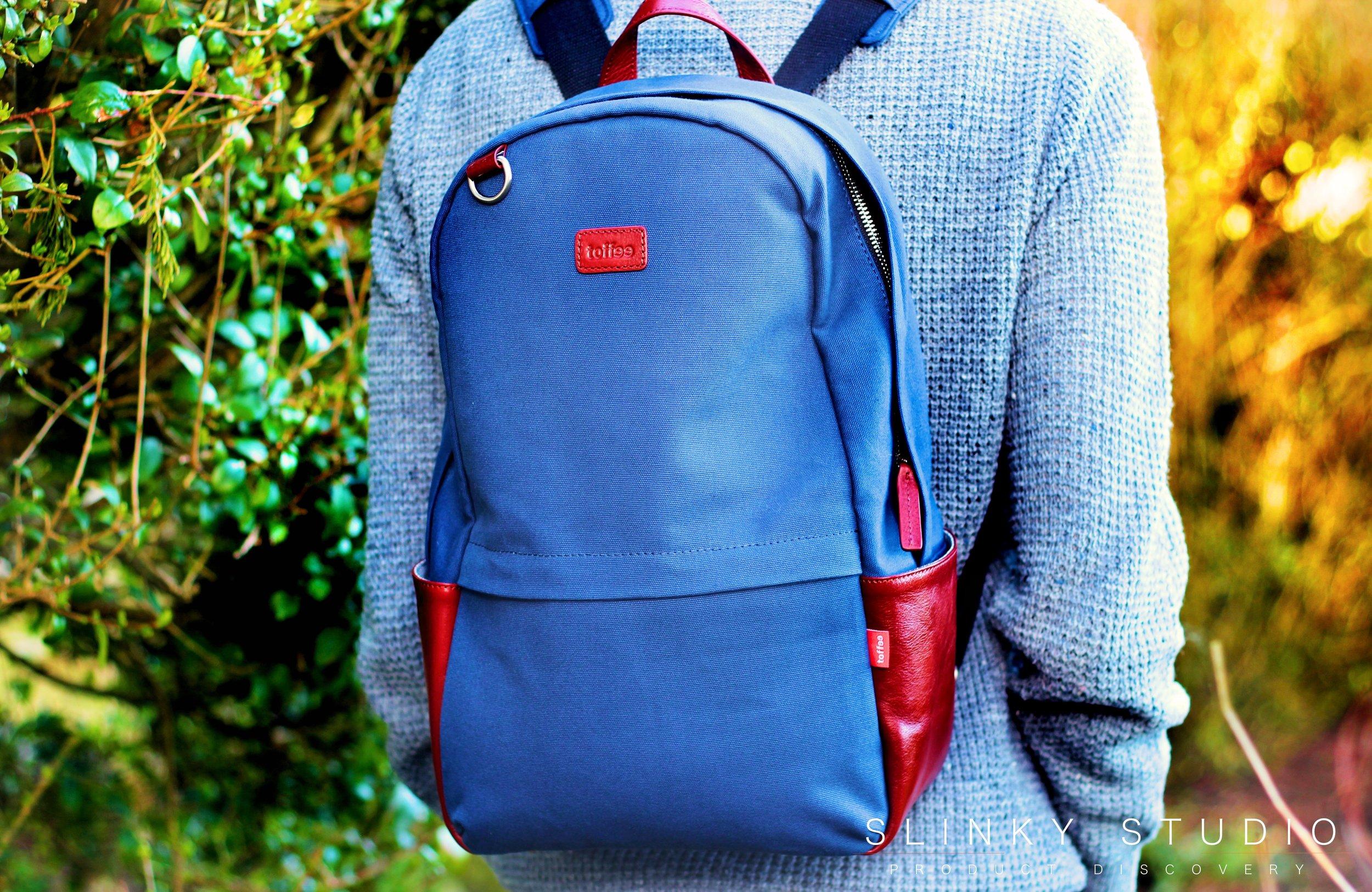 Toffee Berlin Backpack Navy Blue wearing through woodland.jpg