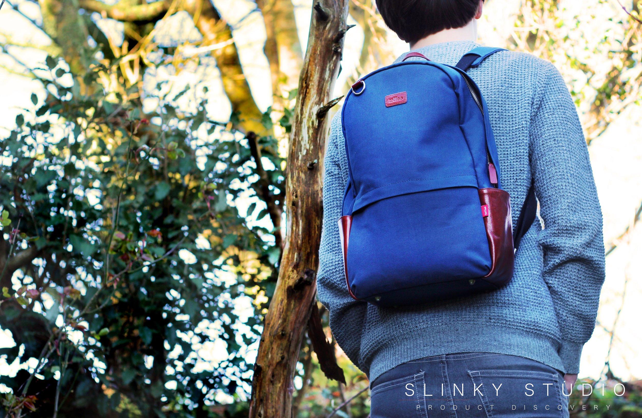 Toffee Berlin Backpack Navy Blue wearing through woodland 2.jpg