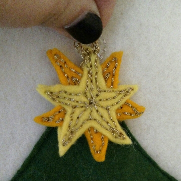 the star--also the only one with a different hanger (all gold).  This is three layers, the darker layer was embroidered separately then sandwiched between the two yellow stars, and the whole shebang embroidered again.