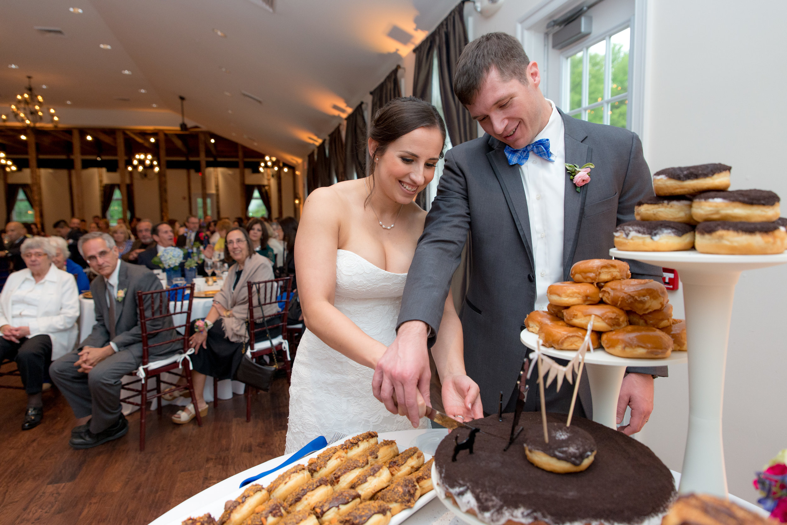 Bride and Groom Cutting a giant donut cake by Sugar Shack