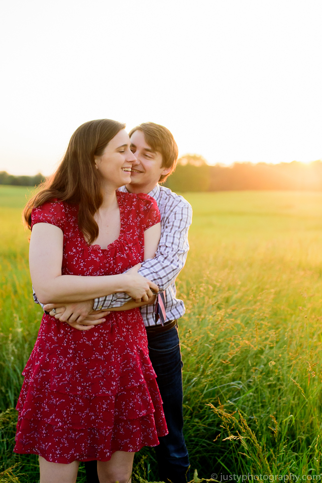 Couple standing in field during sunset engagement session by Washingotn DC photographers Justy Photography