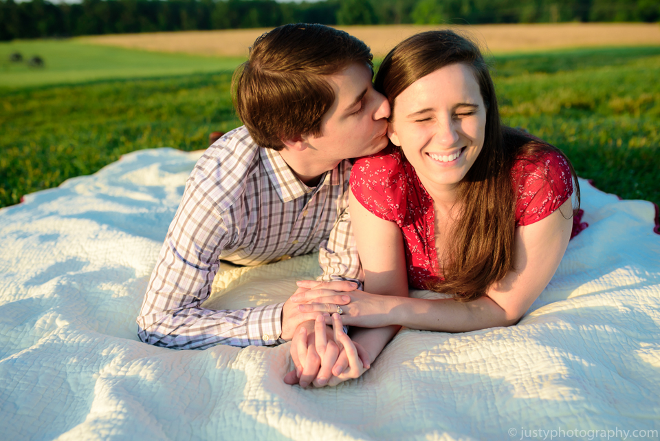Romantic engagement shoot with couple laying on blanket outside.